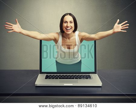 laughing woman come out from laptop and stretching out her hands against dark background