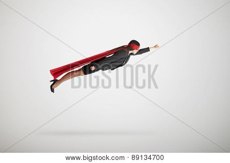 businesswoman dressed as a superhero in red mask and cloak flying over light grey background