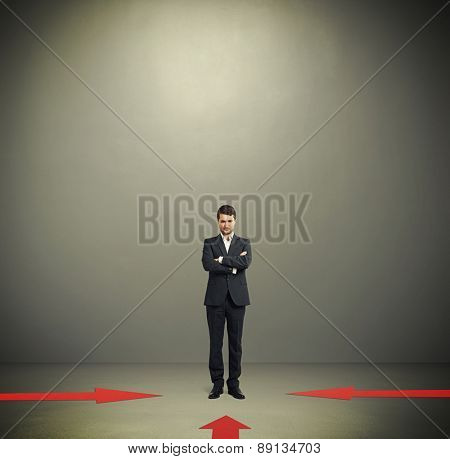 red arrows indicate at pensive businessman in formal wear over dark grey background with empty copyspace overhead