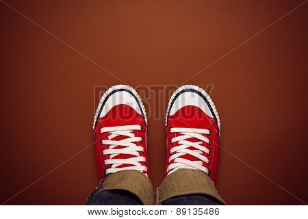 Feet From Above, Teenager In Sneakers Standing On Brown Background