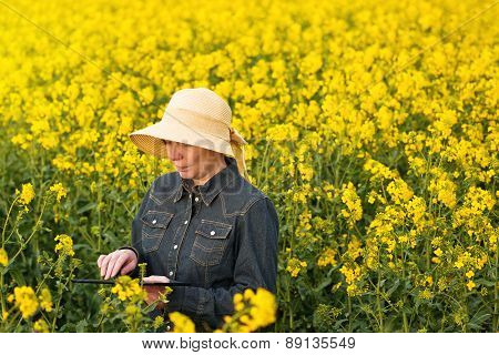 Female Farmer With Digital Tablet In Oilseed Rapeseed Cultivated Field