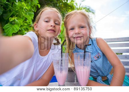 Little girls taking selfie and drinking tasty cocktails at tropical resort