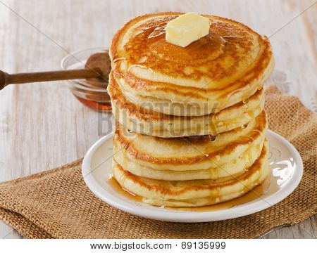 Stack Of Small Pancakes With Maple Syrup On  Wooden Table.
