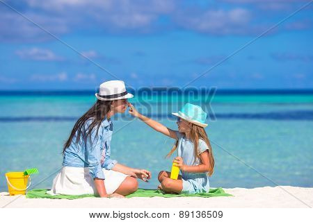 Little adorable girl applying sun cream to her mother nose
