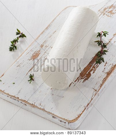 Goat Cheese With Fresh Herbs On A White Wooden Table.