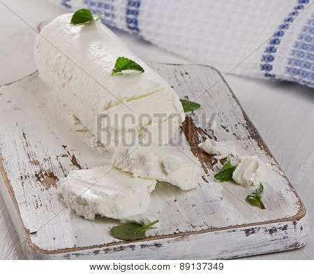Goat Cheese With Herbs On  A White Wooden Table.
