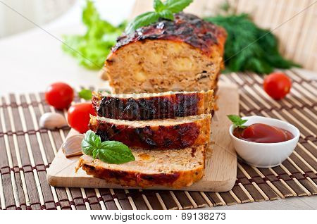 Homemade ground meatloaf with ketchup and basil