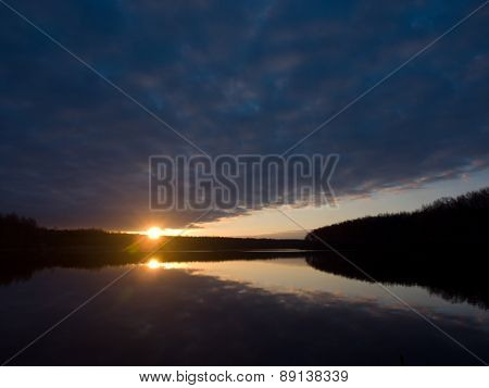 Beautiful sunrise over the forest lake