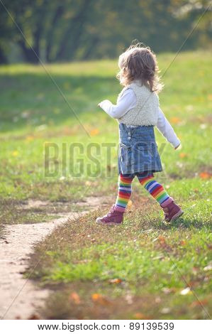 Little Girl Striding Purposefully In The Park