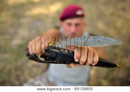 man holding old knife