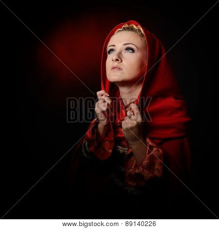 beautiful woman with red cloak posing in studio