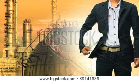 Engineering Man And Safety Helmet Standing Against Oil Refinery Plant In Heavy Petrochemical Industr