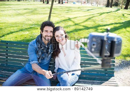 Couple using a selfie stick in a park