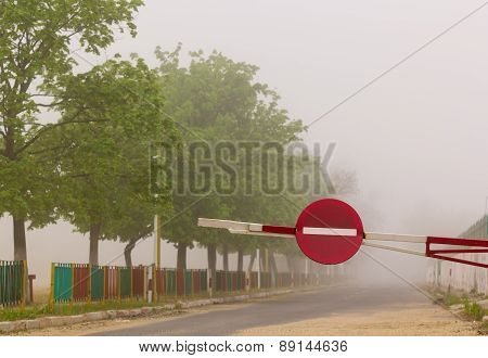 Barrier With No Entry Traffic Sign On Road In Fog