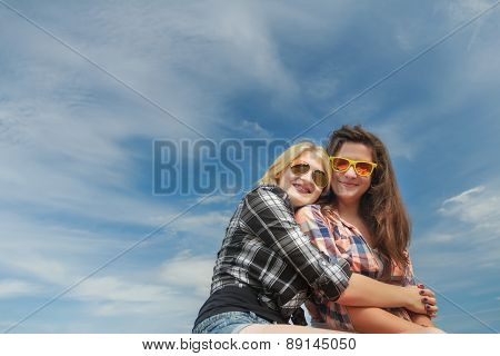 Portrait Of Friends Embracing And Posing To Camera At Cirrus Blue Sky