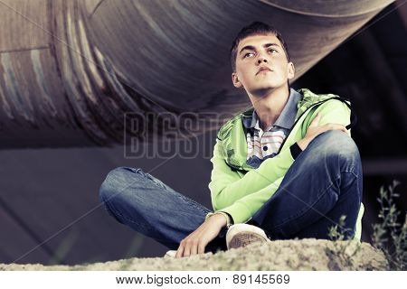 Teen boy in depression sitting on the ground