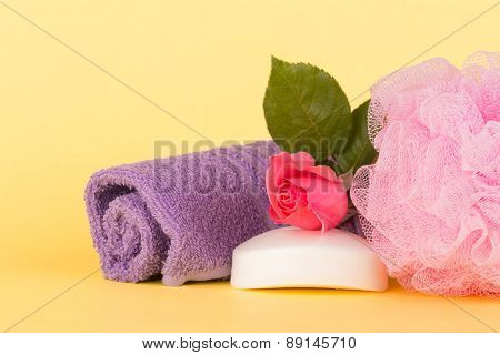 Soap topped with pink rose next to a shower puff and wash cloth against light yellow background