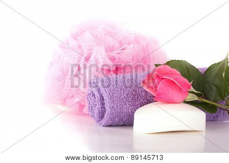 Wash cloth, shower puff, soap and pink rose on light background