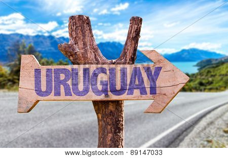 Uruguay wooden sign with road background