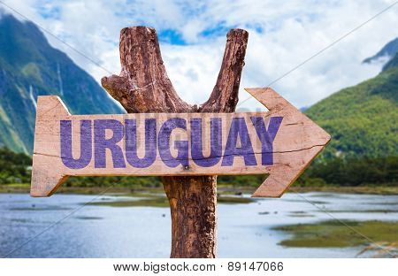 Uruguay wooden sign with countryside background