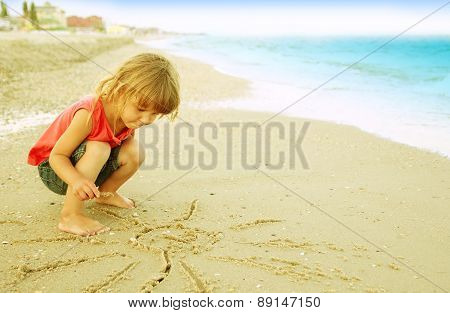Little Girl Draws A Sun In The Sand On The Beach