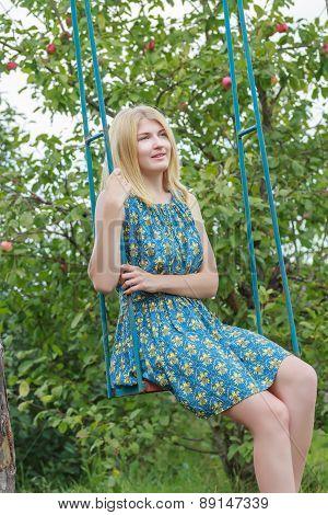 Portrait Of Blonde Girl In Silk Sundress Sitting On Handmade Swing