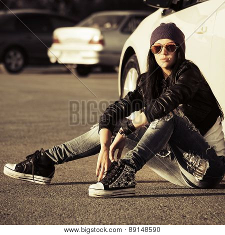 Young fashion punk woman sitting next to her car