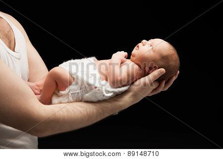 Newborn baby boy on the father's hand.