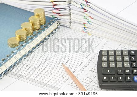 Pencil And Gold Coins On Notebook With Calculator