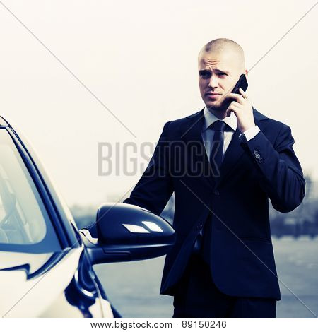 Young businessman calling on the phone next to car