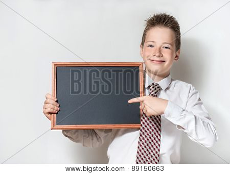 Smiling schoolboy pointing finger at empty chalkboard