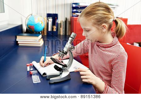 Girl Uses A Microscope And Writes Results
