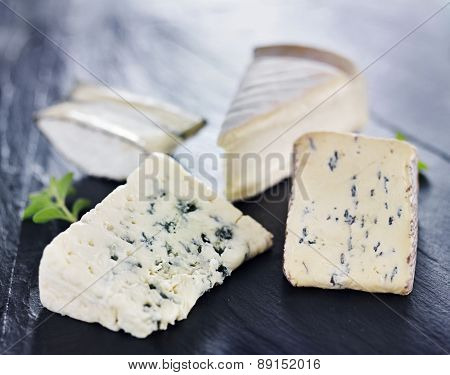 assortment of gourmet artisanal cheeses on slate cheese tray