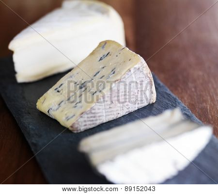 assorted gourmet cheese on slate serving tray