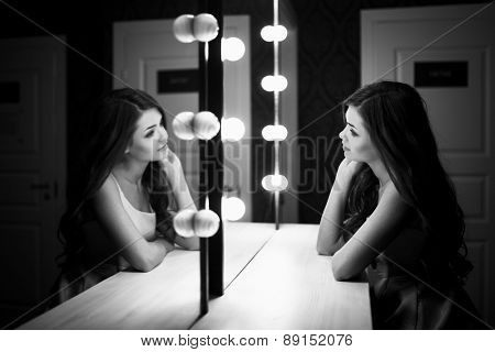 Young beautiful woman with make up and reflection in dressing room. Black and white image.