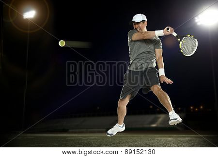 Tennis player during a night match with dark background