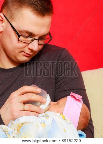 Father Feeding Newborn Baby Girl With Milk Bottle