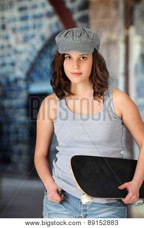 A pretty teen girl looking at the viewer as she's carrying her skateboard in an urban area.