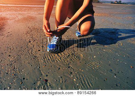 woman runner tying shoelace before running on beach