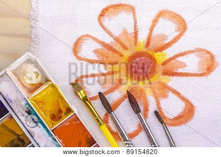 artist's brush on a background painted orange flower