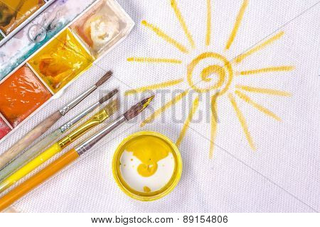 artist's brush on a background painted yellow sun.