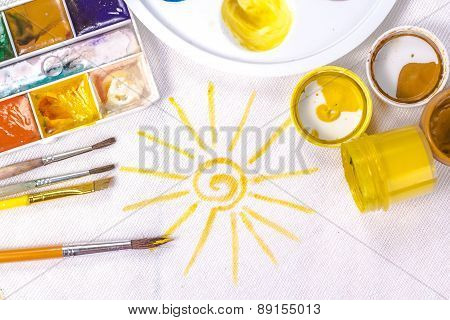 artist's brush on a background painted yellow sun. View from above.