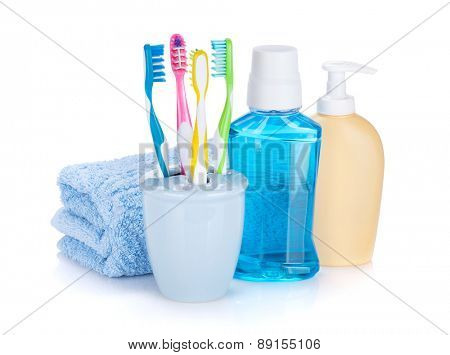 Four colorful toothbrushes, cosmetics bottles and towel. Isolated on white background