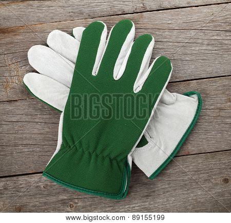 Garden gloves over wooden table background