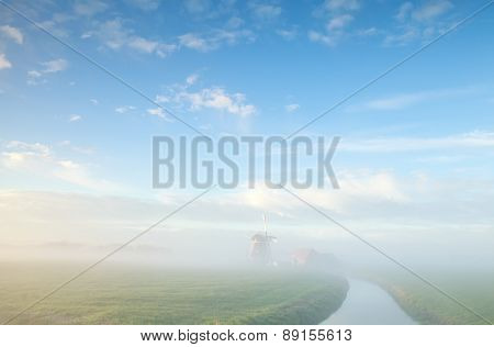 Misty Morning On Dutch Farmland With Windmill