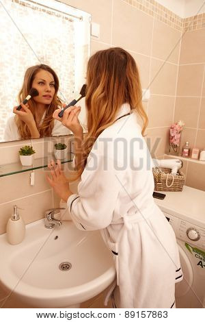 Attractive young woman putting on makeup in the morning using mirror.
