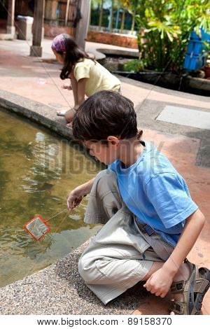 Young boy enjoying a day catching and feeding fish in pond
