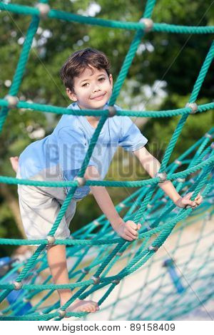 Young boy enjoying on balancing activity at the outdoor park in evening sun.