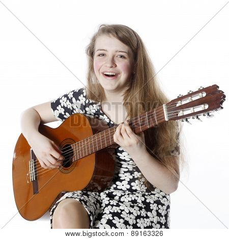 Smiling Teenage Girl In Dress Plays The Guitar In Studio