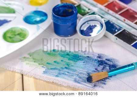 canvas, brushes and cans of blue paint